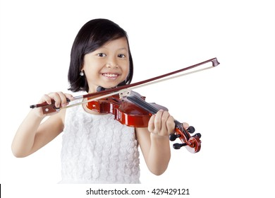 Portrait of a cheerful little girl smiling at the camera while playing a violin in the studio