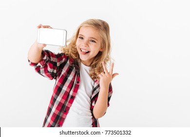 Portrait of a cheerful little girl taking a selfie isolated over white background