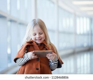 Portrait of cheerful little girl watching cartoon on smartphone