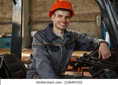 Portrait of cheerful loader in orange hardhat and gray suit sitting on forklift on metal base. Smiling worker putting arm on steering wheel, posing and looking at camera. Young man enjoying his job.