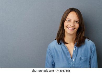 Portrait of cheerful long-haired woman against grey background