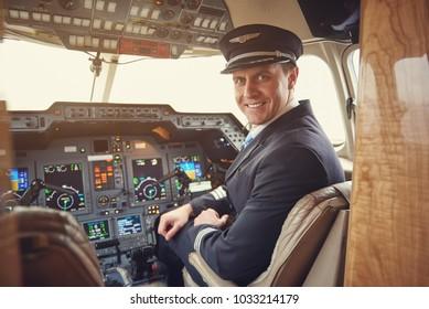 Portrait of cheerful male aviator in uniform sitting in cockpit. Job concept