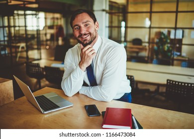 Portrait of cheerful male economist in formal wear sitting at desktop with laptop device and smartphone and looking at camera, successful man employee spending time in office and waiting colleague