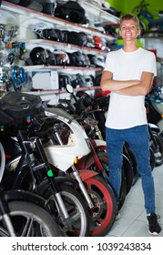 Portrait of cheerful male standing near the bike in the motorcycle shop