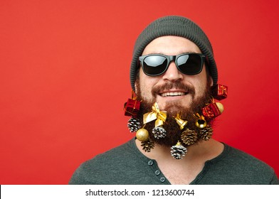 Portrait of cheerful man with beard looking at the camera over red background