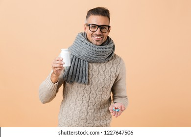 Portrait of a cheerful man dressed in sweater and scarf standing isolated over beige background, showing pills capsules