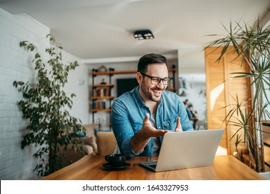 Portrait of a cheerful man having video call on laptop computer.