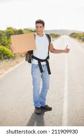 Portrait of a cheerful man hitchhiking with cardboard on countryside road