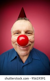 Portrait of a cheerful man with red nose smiling at camera on fool�s day