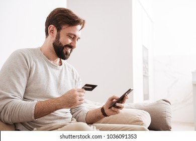 Portrait of a cheerful man shopping online with credit card and mobile phone while sitting on a couch at home
