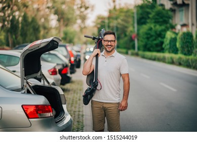 Portrait of a cheerful man standing near the car with folded electric scooter on his shoulder.