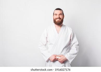 Portrait von fröhlichem Mann Taekwondo-Instruktor, der die Kamera auf weißem Hintergrund anschaut und lächelt.