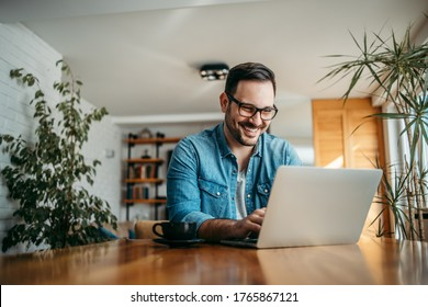 Portrait of a cheerful man using laptop while sitting at wooden table at cozy home.