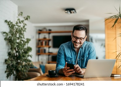 Portrait of a cheerful man using smart phone at home office.