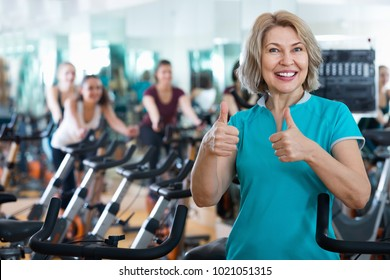 Portrait of cheerful mature blonde smiling in exercise bikes class