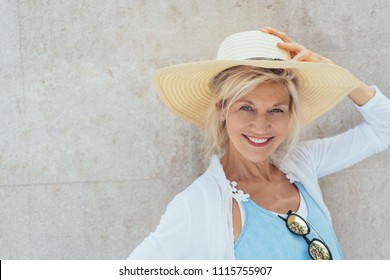 Portrait of cheerful mature blonde woman wearing summer hat