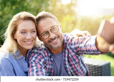 Portrait of cheerful mature couple taking selfie picture