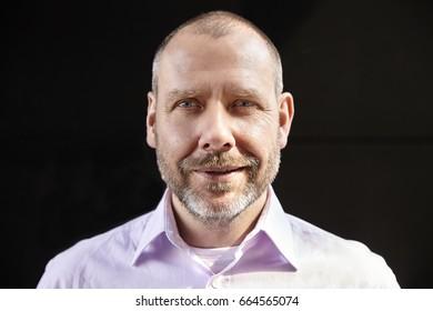 Portrait of cheerful mature man on black background.