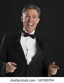 Portrait of cheerful mature man in tuxedo gesturing against black background