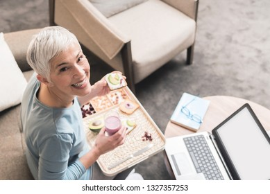 Portrait of cheerful mature woman with beautiful smile and full of energy eating a healthy nutritious breakfast meal, Healthy lifestyle concept