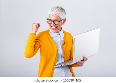 Portrait of a cheerful mature woman with a laptop computer and celebrating success isolated over gray background. Senior lady watching celebrating online bid bet win or great result victory concept