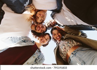 Portrait of cheerful men and women forming a huddle against sky. Happy group of friends huddling outdoors.