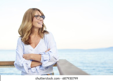 Portrait of a cheerful middle aged woman standing with arms crossed at the sea.