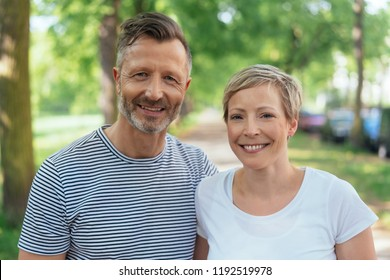 Portrait of a cheerful middle-age couple in love looking at camera with joy outdoors in a summer day