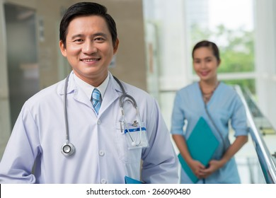 Portrait of cheerful middle-aged doctor, his assistant is in background
