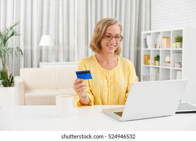 Portrait of cheerful middle-aged woman shopping online from home