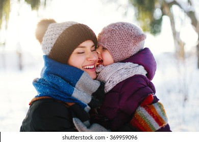 Portrait of a cheerful mother and her daughter in a winter forest at sunset. Focus on the child