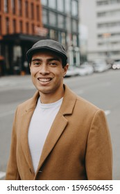 Portrait of cheerful nice happy young man outside. Arabian or egyptian guy look on camera and smile. Wear white shirt, brown jacket and grey cap. Walking on road alone