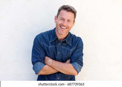 Portrait of cheerful older man standing with arms crossed
