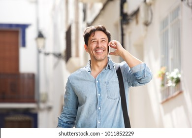Portrait of cheerful older man walking outdoors and making a phone call