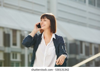 Portrait of cheerful older woman sitting outside talking on phone in city