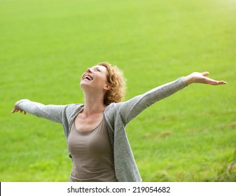 Portrait of a cheerful older woman smiling with arms outstretched