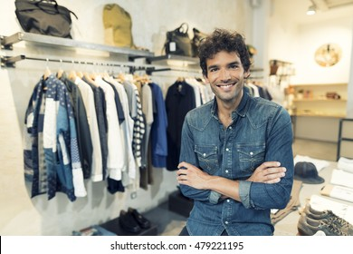 Portrait of cheerful owner in clothing store. Looking at camera