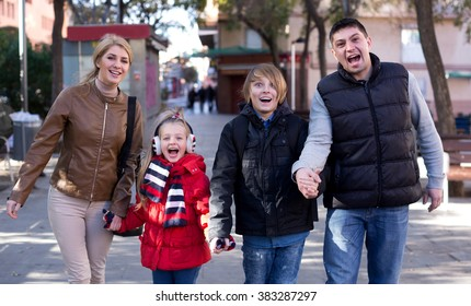 Portrait cheerful parents with children posing outdoor in cold day and smiling
