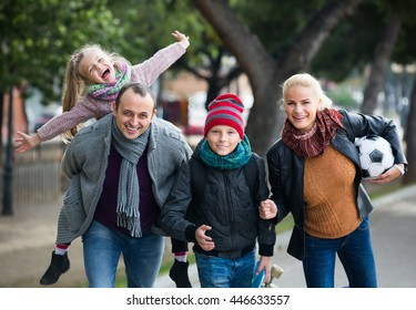 Portrait of cheerful parents with school age children spending time together outdoors