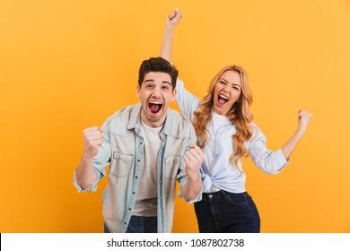 Retrato de personas alegres, hombres y mujeres con ropa básica, sonriendo y apretando los puños como ganadores o personas felices aisladas sobre un fondo amarillo