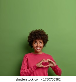 Portrait of cheerful pleasant looking Afro American woman shows heart sign over chest, expresses love and care, looks above, wears pink jumper, poses against green background, empty space upwards