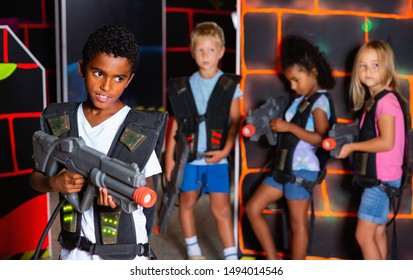Portrait of cheerful positive  african preteen boy standing with laser gun on dark lasertag arena on background with his team
