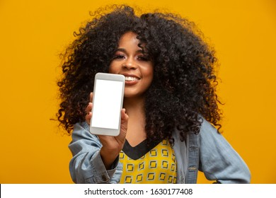 Portrait of cheerful, positive, attractive young woman in jeans shirt, having smart phone with white screen in hand, pointing with forefinger to product, isolated on yellow background