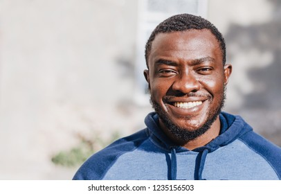 Portrait of a cheerful positive black guy close-up in a sports sweater on the background of an urban house. Race issues. City photo, space. Youthful culture.