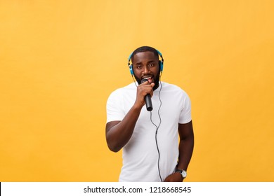 Portrait of cheerful positive chic handsome african man holding microphone and having headphones on head listening music singing song enjoying weekend vacation isolated on yellow background
