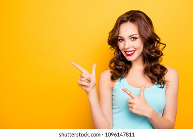 Portrait of cheerful positive coquette gesturing two forefingers showing copy space empty place looking at camera isolated on yellow background, advertisement concept