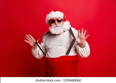 Portrait of cheerful positive dreamy funky Santa congratulations best wishes pulling suspenders ready to feast congrats isolated over bright vivid red background