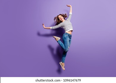 Portrait of cheerful positive girl jumping in the air with raised hands and leg looking at camera isolated on violet background. Life lifestyle energy people concept