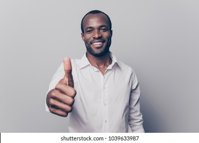 Portrait of cheerful, positive, handsome man with black skin, beaming smile in white shirt showing thumb up with finger to the camera isolated on grey background