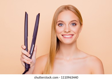 Portrait of cheerful positive joyful model with clean clear fresh skin beaming smile having straightener in hand looking at camera isolated on beige background